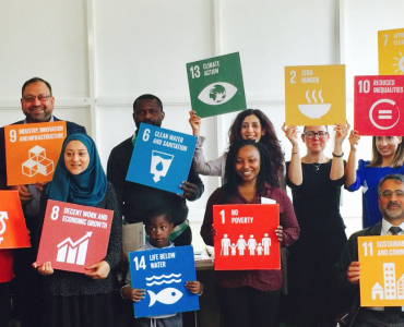 CEMVO Equalities Event attendees posing with SDG cards