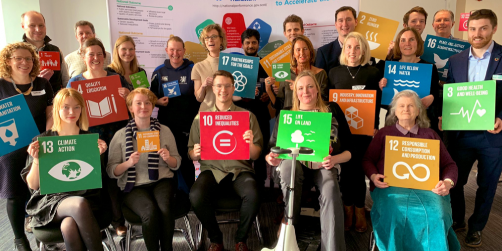 Group photo of participants at SDG Network Workshop holding the SDGs Boards